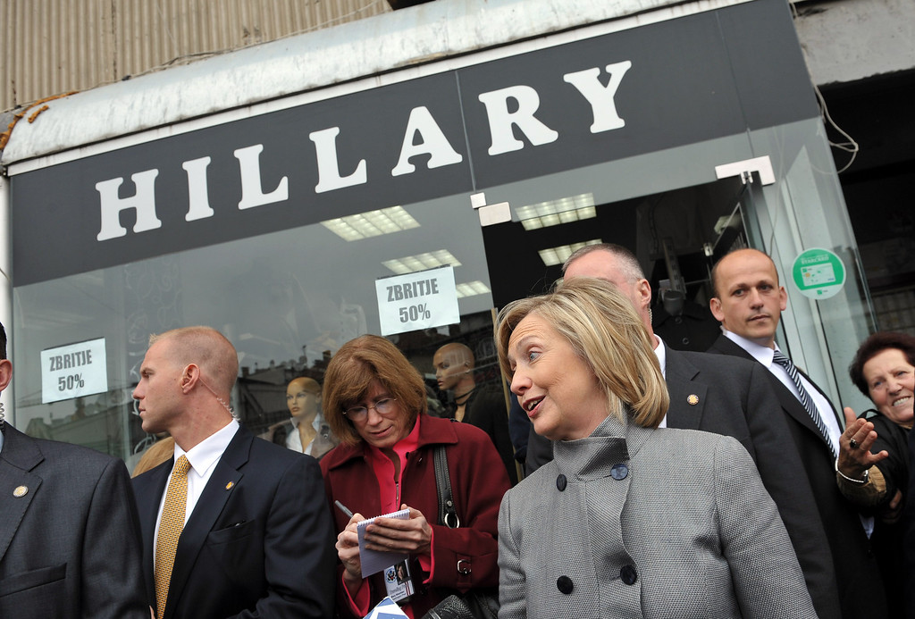. U.S. Secretary of State Hillary Rodham Clinton smiles as she walks out of a store named in her honor, which is located next to an unseen statue of her husband, in Pristina, Kosovo, Wednesday Oct. 13, 2010.  (AP Photo/Mandel Ngan, Pool)