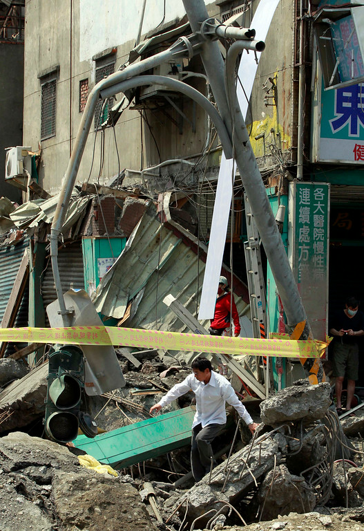 . A man moves through a street destroyed by a massive gas explosion in Kaohsiung, Taiwan, Friday, Aug. 1, 2014. Scores of people were killed and more than 200 others injured when several underground gas explosions ripped through Taiwan\'s second-largest city overnight, hurling concrete through the air and blasting long trenches in the streets, authorities said Friday. (AP Photo/Wally Santana)
