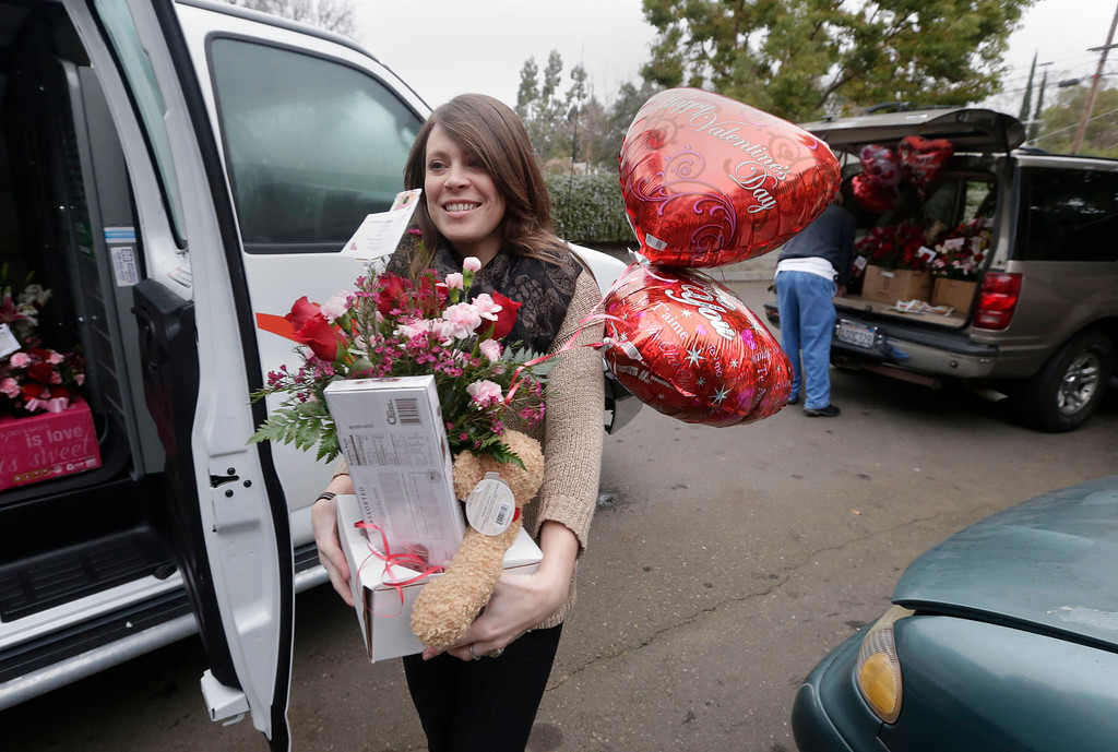 . Kristen Ullery, of East Lawn Florists, carries a Valentines Day flower arrangement to a van for delivery in Sacramento, Calif., Friday, Feb. 14, 2014.(AP Photo/Rich Pedroncelli)