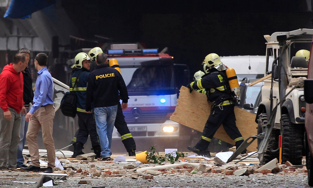 . Policemen and firefighters inspect the scene of an explosion in downtown Prague, Czech Republic, Monday, April 29, 2013.  Police said a powerful explosion has damaged a building in the center of the Czech capital and they believe some people are buried in the rubble. (AP Photo/Petr David Josek)
