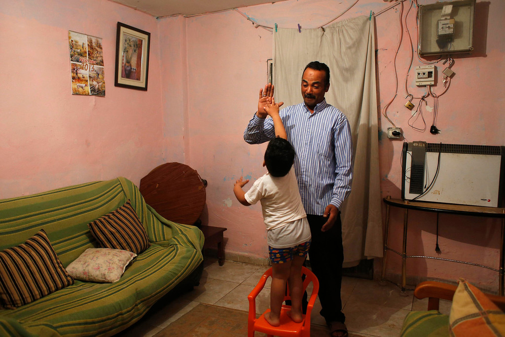 . Farm worker Mustapha El-Mezroui high fives his three-year-old son Bilal in the living room of their home on a farm belonging to Spanish farmer Santiago Perez outside La Puebla, in the southern Spanish region of Murcia June 5, 2013. El-Mezroui left his native Morocco for Spain on a makeshift boat in the mid-1990s, and now works as a keeper and farm hand on a farm outside La Puebla, Cartagena, where he lives with his wife and three-year-old son. He supervises day labourers, does maintenance work and performs other jobs, helping to keep the farm secure. The majority of day labourers in the region come from Morocco and Ecuador, and it can be rare to see Spanish labourers in the fields. Nevertheless, as Spain wrestles with economic crisis and youth unemployment levels above 50 percent, some young Spaniards are starting to consider the kinds of jobs mostly performed by immigrants during the boom years Picture taken June 5, 2013. REUTERS/Susana Vera