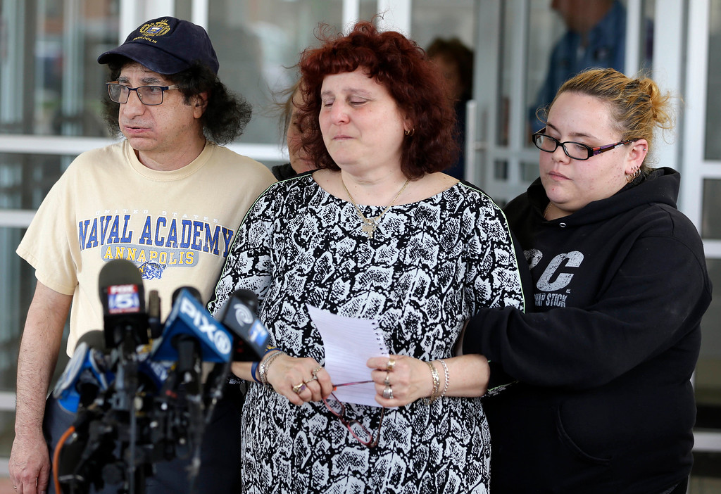 . Surrounded by friends and family, Susan Zemser, center, and Howard Zemser, the parents of U.S. Naval Academy Midshipman Justin Zemser, prepare to speak to the media outside their home in New York, Wednesday, May 13, 2015. Zemser, 20, who was on leave and heading home to Rockaway Beach, N.Y., was killed when an Amtrak passenger train derailed and overturned in Philadelphia on the nation\'s busiest rail corridor Tuesday night.  (AP Photo/Seth Wenig)