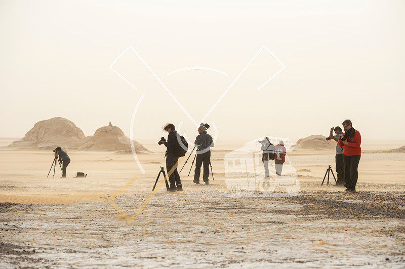 Landscape photographers in a sandstorm in the Egyptian white desert national park during a photography tour
