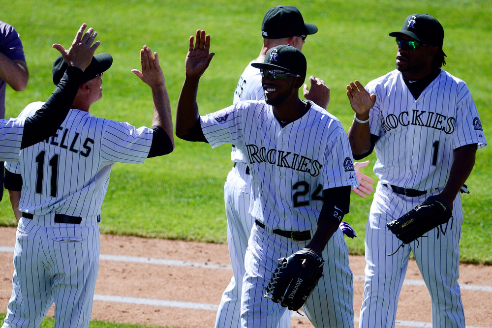 . Colorado Rockies center fielder Dexter Fowler (24) high-fives teammates after his two home run performance against the Los Angeles Dodgers following the Rockies\' 7-2 win in Denver. The Colorado Rockies hosted the Los Angeles Dodgers at Coors Field. (Photo by AAron Ontiveroz/The Denver Post)