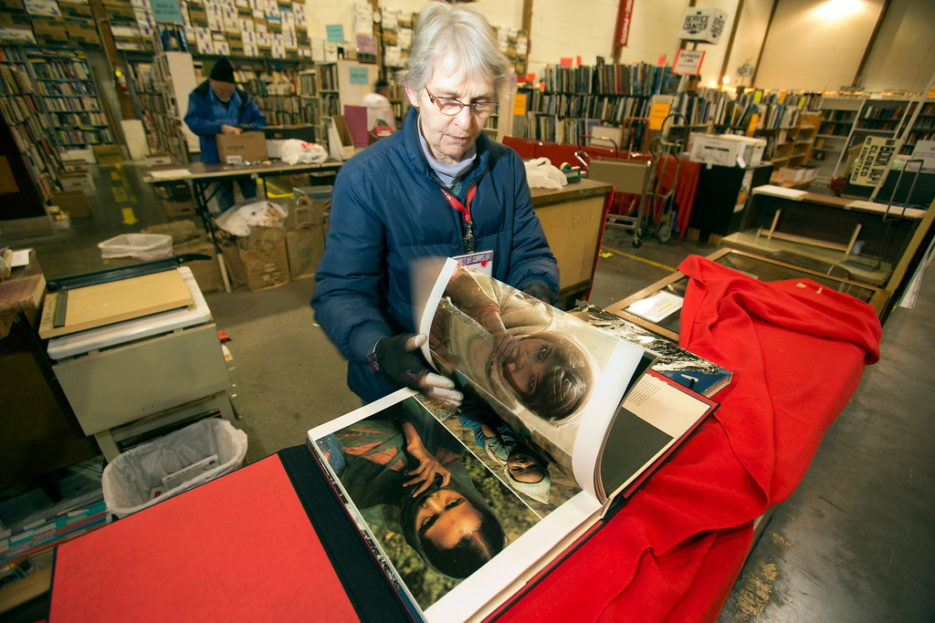 . Rose Jellison, the books chair for the annual White Elephant Sale, leafs through a first edition photography book of images from the Himalayas at the Oakland Museum Women\'s Board 96,000-square-foot warehouse in Oakland, Calif., Tuesday, Jan. 15, 2013. (D. Ross Cameron/Staff)