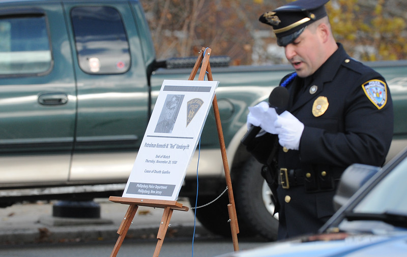 """Phillipsburg Police Sgt. James McDonald stands next to a memorial board as he reads the account of of Vandegrift's death in 1930. The Phillipsburg Police Department held a remembrance ceremony honoring fallen officer, Kenneth W. """"Red"""" Vandegrift who died in the line of duty Nov. 20, 1930. The ceremony was at the bridge on South Main Street that bears his name."""