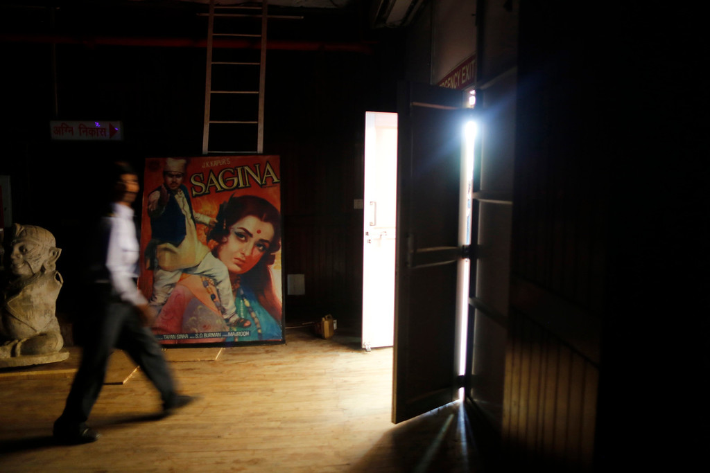 """. A security guard walks past a Hindi movie poster at an auditorium during a festival celebrating 100 years of Indian cinema in New Delhi April 30, 2013. Indian cinema marks 100 years since Dhundiraj Govind Phalke\'s black-and-white silent film \""""Raja Harishchandra\"""" (King Harishchandra) held audiences spellbound at its first public screening on May 3, 1913, in Mumbai. Indian cinema, with its subset of Bollywood for Hindi-language films, is now a billion-dollar industry that makes more than a thousand films a year in several languages. It is worth 112.4 billion rupees (over $2 billion) and leads the world in terms of films produced and tickets sold. Picture taken April 30, 2013. REUTERS/Anindito Mukherjee"""