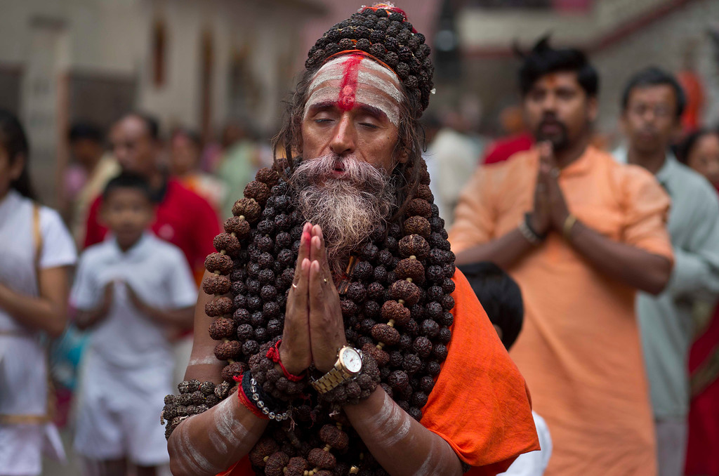 . An Indian Sadhu or Hindu holy man performs Yoga as others follow during the International Yoga Day at Kamakhya temple in Gauhati, India, Wednesday, June 21, 2017. Millions of yoga enthusiasts across India take part in a mass yoga sessions to mark the third International Yoga Day which falls on June 21 every year. (AP Photo/ Anupam Nath)