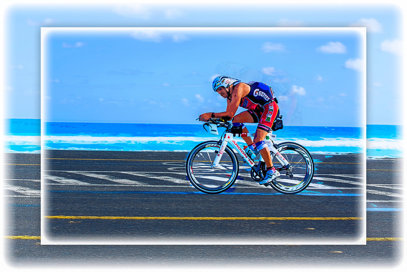 Against the Wind… A lone cyclist sports the colors of Mexico and rides into the wind during the 112-mile cycling stage of Ironman Cozumel 2013 along Playa Oriente near Mezcalitos on the east side of the island. An artistic white frame treatment has been added to this image, which is otherwise identical to the adjacent one.