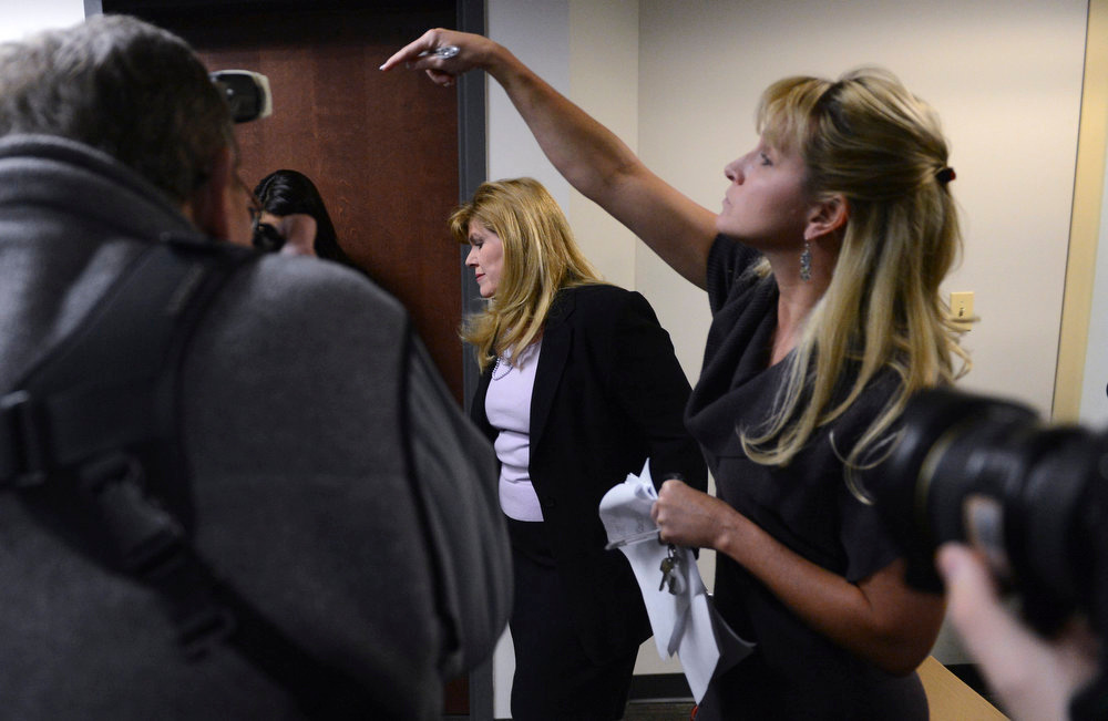 . Assistant District Attorney Karen Pearson, of the prosecution team, makes here way through the media heading into court, Monday, January 7, 2013, in Centennial. RJ Sangosti, The Denver Post