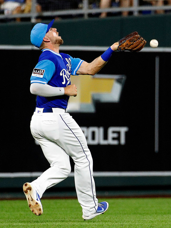 . Kansas City Royals third baseman Hunter Dozier misses a fly ball for a single by Cleveland Indians\' Michael Brantley during the fifth inning of a baseball game Friday, Aug. 24, 2018, in Kansas City, Mo. (AP Photo/Charlie Riedel)