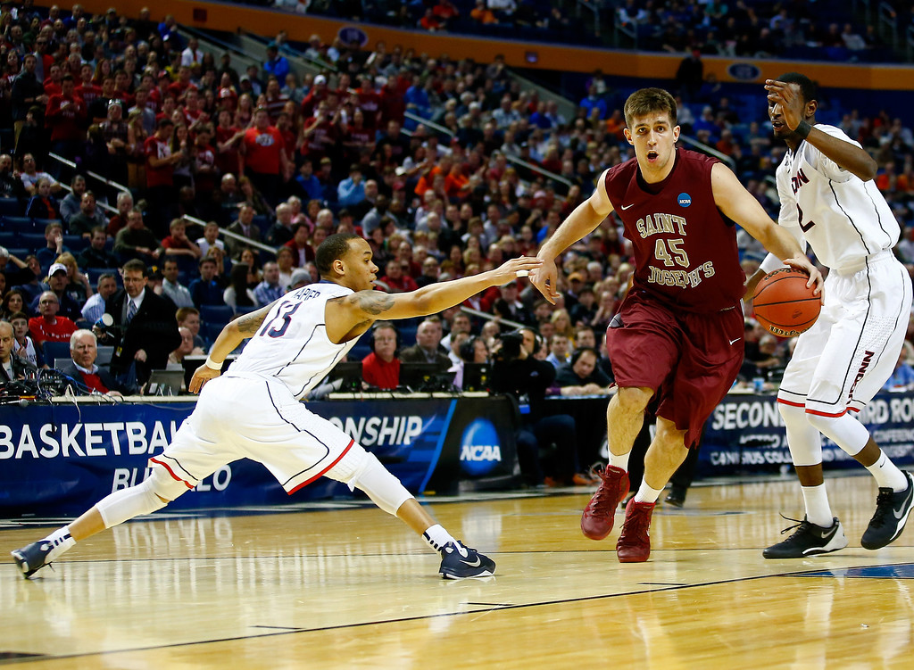 . BUFFALO, NY - MARCH 20: Halil Kanacevic #45 of the Saint Joseph\'s Hawks is fouled by Shabazz Napier #13 of the Connecticut Huskies on his way to the basket during the second round of the 2014 NCAA Men\'s Basketball Tournament at the First Niagara Center on March 20, 2014 in Buffalo, New York.  (Photo by Jared Wickerham/Getty Images)