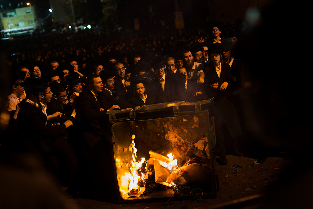 . Ultra-orthodox jews push a burning garbage bin towards Israeli security forces during a protest against military conscription of yeshiva students, in Jerusalem, Thursday, May 16, 2013. (AP Photo/Bernat Armangue)