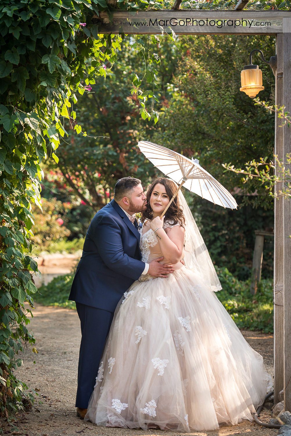 groom in blue suit kissing bride holding white umbrella at Taber Ranch Vineyards
