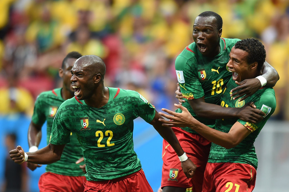 . Cameroon\'s midfielder Joel Matip (R) celebrates with Cameroon\'s defender Allan Nyom (L) and Cameroon\'s forward Vincent Aboubakar after scoring a goal during the Group A football match between Cameroon and Brazil at the Mane Garrincha National Stadium in Brasilia during the 2014 FIFA World Cup on June 23, 2014.  VANDERLEI ALMEIDA/AFP/Getty Images