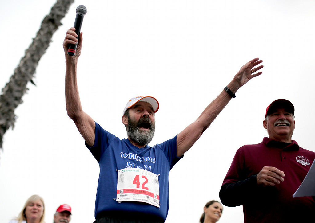 . Tom Wichelmann ramps up the crowds on Beach Street in Santa Cruz on Sunday while wearing the number 42 on his bib to represent the 42 years he\'s ran the Wharf to Wharf. (Kevin Johnson -- Santa Cruz Sentinel)