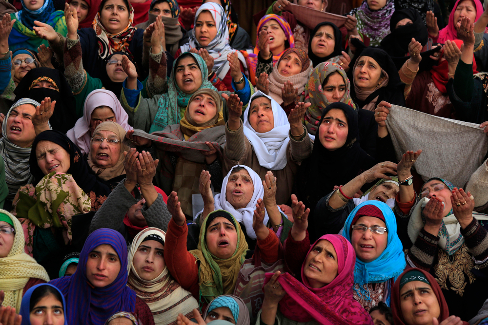 . Kashmiri Muslim devotees raise their hands in prayer as a head priest displays a relic of Prophet Muhammad at the Hazratbal shrine on Eid-e-Milad, or birth anniversary of the prophet, in Srinagar, India, Tuesday, Jan. 14, 2014. Thousands of Kashmiri Muslims gathered at the Hazratbal shrine, which houses a relic believed to be a hair from the beard of the prophet. (AP Photo/Dar Yasin)