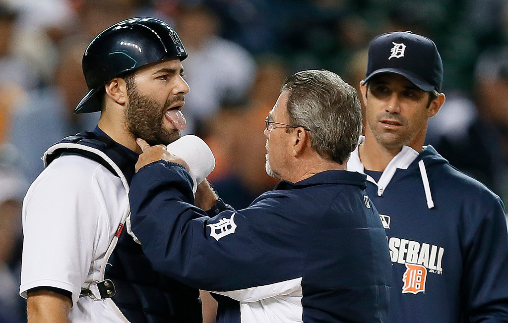 . Detroit Tigers trainer Kevin Rand checks Detroit Tigers catcher Alex Avila, left, after being hit by a ball as manager Brad Ausmus looks on against the Minnesota Twins in the eighth inning of a baseball game in Detroit, Friday, Sept. 26, 2014. (AP Photo/Paul Sancya)