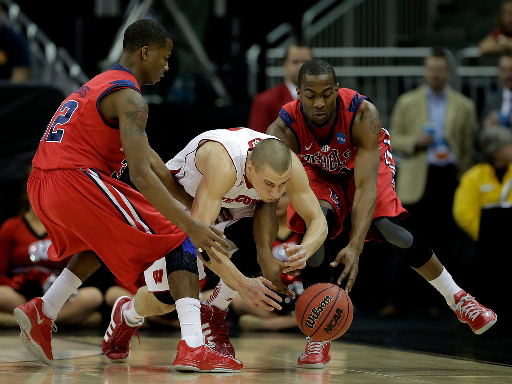 . Wisconsin guard Ben Brust, center, battles Mississippi guards Jarvis Summers, left, and Ladarius White, right, for a loose ball during the first half of a second-round game of the NCAA college basketball tournament Friday, March 22, 2013, in Kansas City, Mo. (AP Photo/Charlie Riedel)