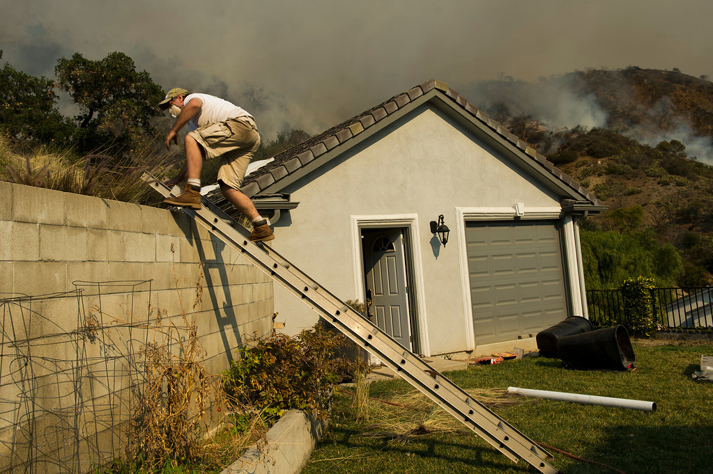 . Mark Davis runs water hoes around his home to defend it from the wildfire burning on Hicrest Road in Glendora, Calif. on Thursday, Jan. 16, 2014. (Photo by Watchara Phomicinda/ San Gabriel Valley Tribune)