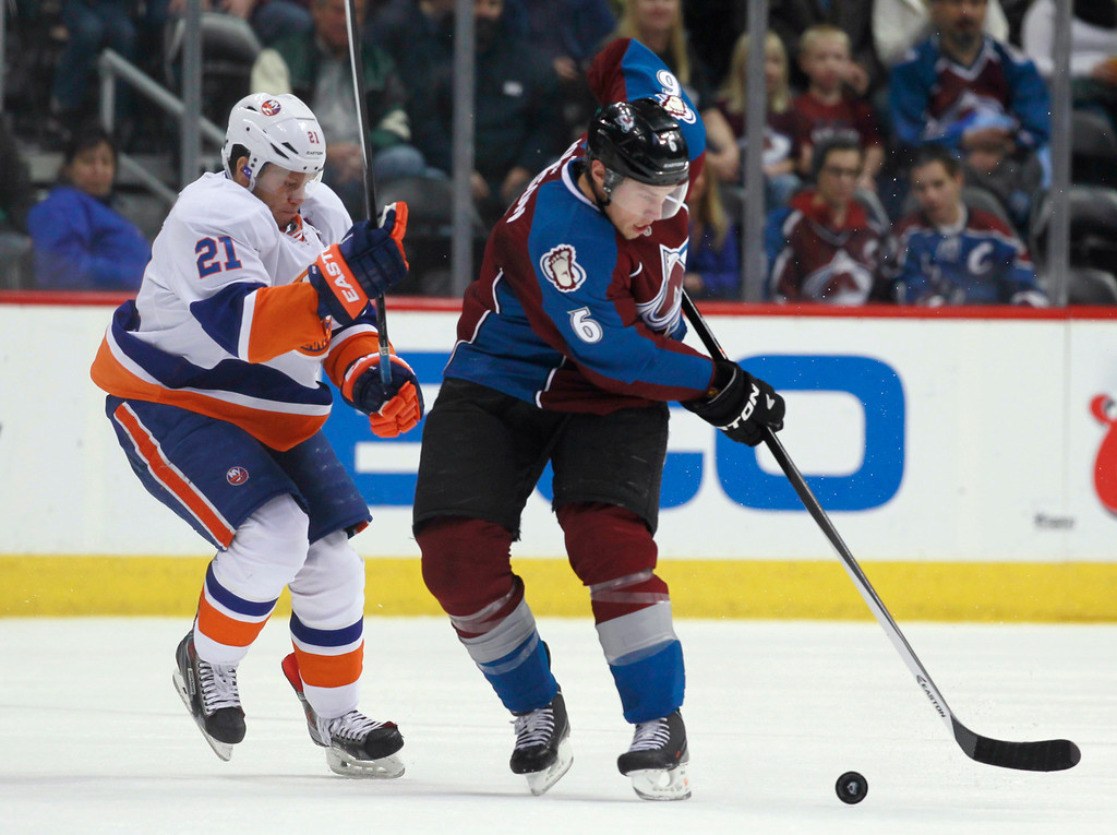 . Colorado Avalanche defenseman Erik Johnson, right, struggles to corral a loose puck as New York Islanders right wing Kyle Okposo defends during the first period of an NHL hockey game in Denver on Friday, Jan. 10, 2014. (AP Photo/David Zalubowski)