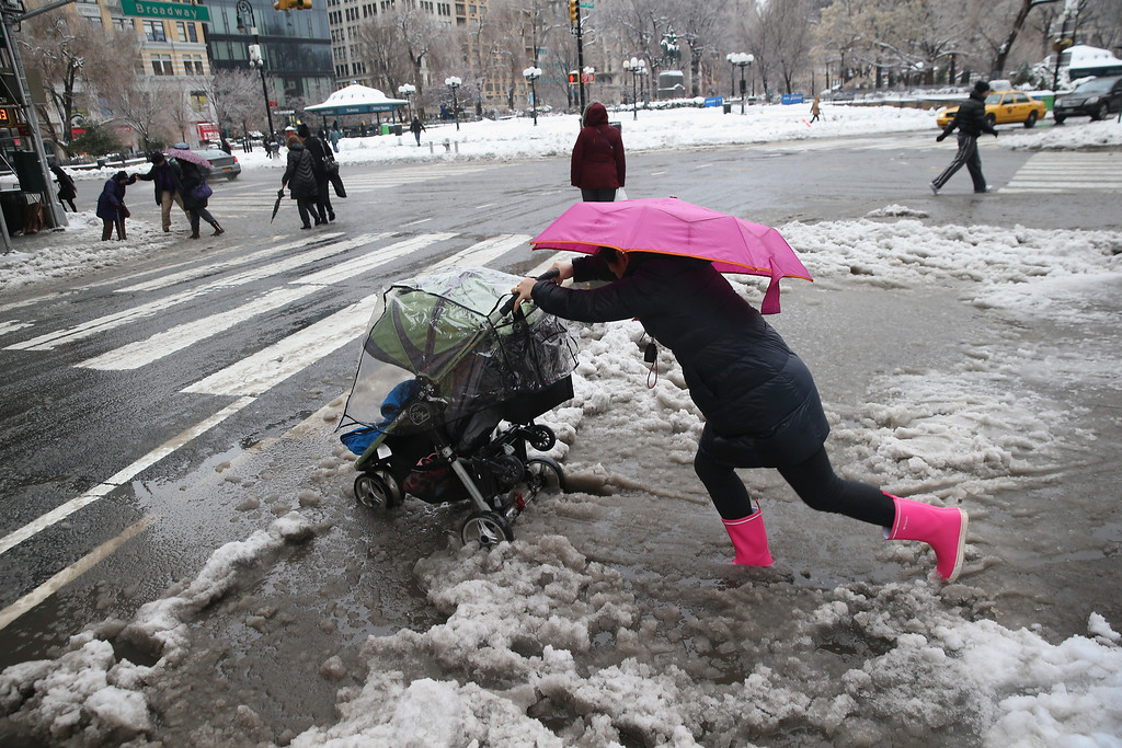 . A nanny pushes a child through the slushy intersection of Broadway and 14th Street at Union Square on February 5, 2014 in New York City. New Yorkers, like millions of Americans in the northeast, dealt with the latest winter storm, which dumped 4 inches of snow on Central Park before turning to rain.  (Photo by John Moore/Getty Images)