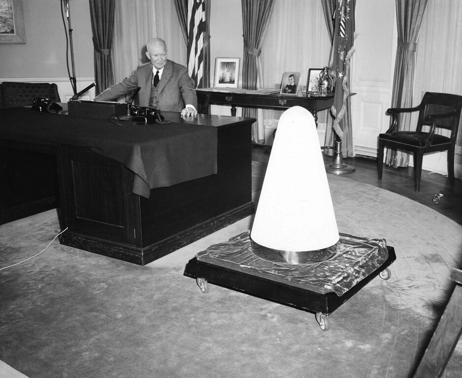 . President Dwight D. Eisenhower, in his White House office, looks toward the nose cone of an experimental missile which he said had been hundreds of miles to outer space and returned to earth completely intact, Nov. 7, 1957.  The president spoke on a nationally televised broadcast on the subject of Science and Security.  (AP Photo/Charles Gorry)