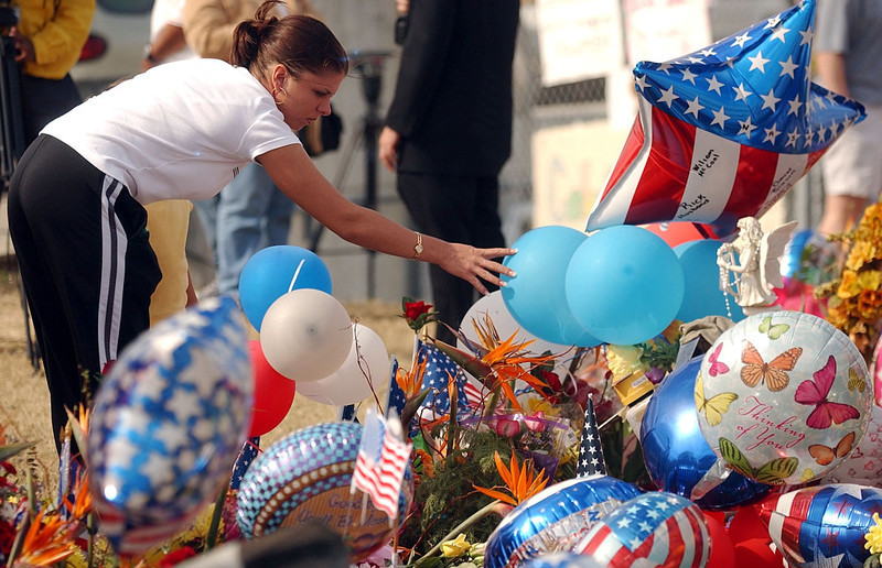 . Cynthia Gallegos of Houston, reaches out to touch balloons that are part of a memorial to  space shuttle Columbia astronauts who died on Saturday as their space ship exploded over Texas during reentry. Gallegos brought her daughter Sierra  to the Lyndon B. Johnson Space Center to honor the astronauts who died. CYRUS MCCRIMMON, The Denver Post