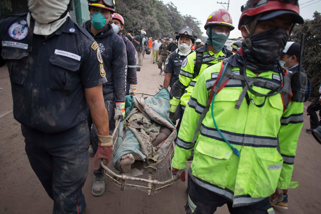 ". Firefighters carry a body recovered near the Volcan de Fuego, or ""Volcano of Fire,\"" in Escuintla, Guatemala, Monday, June 4, 2018. A fiery volcanic eruption in south-central Guatemala sent lava flowing into rural communities, killing at least 25 as rescuers struggled to reach people where homes and roads were charred and blanketed with ash. (AP Photo/Luis Soto)"