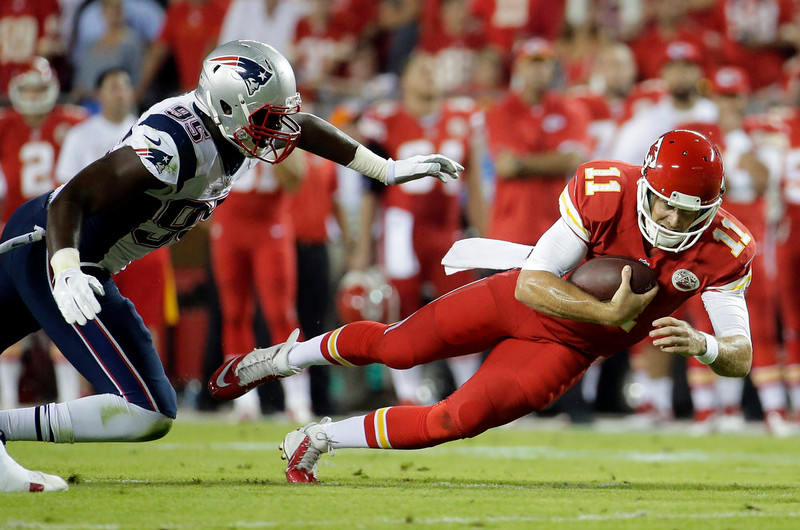 . Kansas City Chiefs quarterback Alex Smith, right, scrambles for yardage as New England Patriots defensive end Chandler Jones defends during the first quarter of an NFL football game Monday, Sept. 29, 2014, in Kansas City, Mo. (AP Photo/Charlie Riedel)