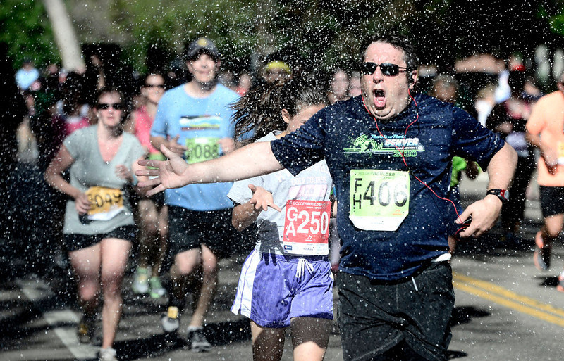 . Fabrice Durand of Denver cools off in the spray during the 2013 Bolder Boulder in Boulder Colorado.  Photo by Paul Aiken / The Boulder Daily Camera / May 27, 2013