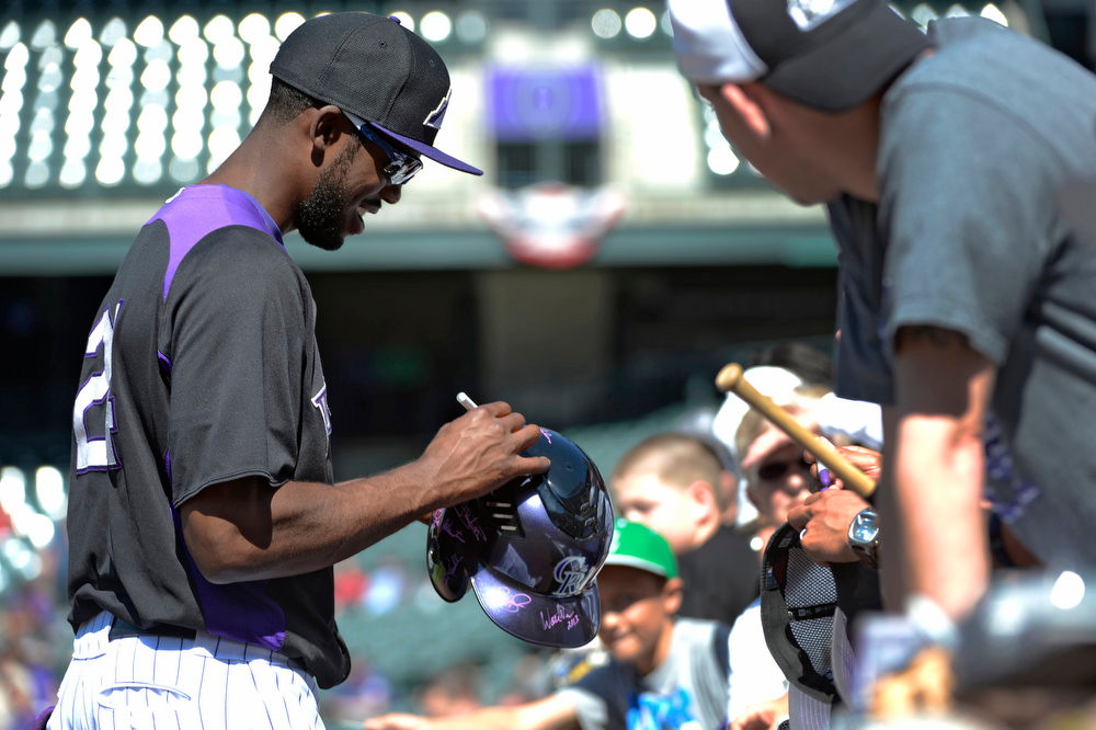. Colorado Rockies Dexter Fowler signs autographs for fans during their batting practice. The Colorado Rockies held an open practice for the fans April 4, 2013 at Coors Field. (Photo By John Leyba/The Denver Post)