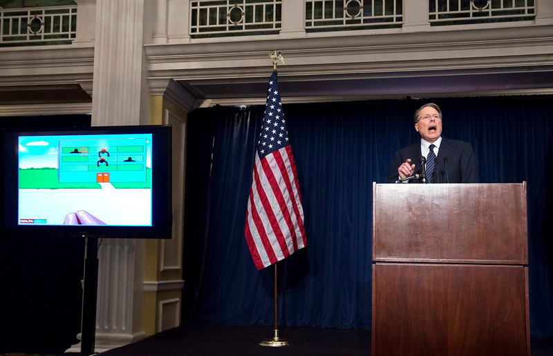 . Wayne LaPierre, executive vice president of the National Rifle Association (NRA), shows a violent video game during a news conference in Washington December 21, 2012. NRA, the powerful U.S. gun rights lobby, went on the offensive on Friday arguing that schools should have armed guards, on a day that Americans remembered the victims of the Newtown, Connecticut school massacre with a moment of silence. REUTERS/Joshua Roberts