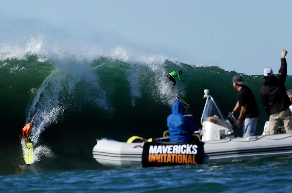 Description of . Spectators cheer on Nathan Fletcher, left, and Rusty Long as they compete during a semifinal heat at the Mavericks Invitational big wave surf contest in Half Moon Bay, Calif., Sunday, Jan. 20, 2013. (AP Photo/Marcio Jose Sanchez)