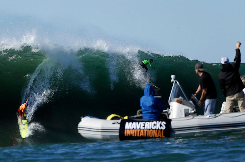 . Spectators cheer on Nathan Fletcher, left, and Rusty Long as they compete during a semifinal heat at the Mavericks Invitational big wave surf contest in Half Moon Bay, Calif., Sunday, Jan. 20, 2013. (AP Photo/Marcio Jose Sanchez)