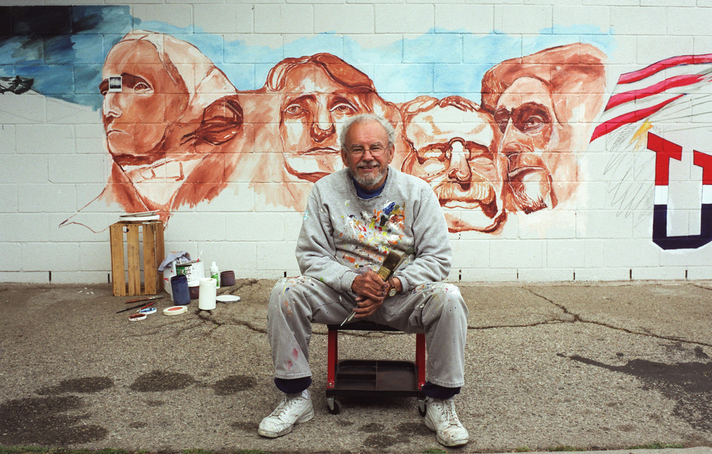 """. 2002 file photo of Alfredo Diaz Flores in front one of his murals in Arleta. Flores passed away in 2008 and his mural \""""Panorama: G.M. Recollections from the Past,\"""" on Van Nuys Boulevard in Panorama City is being restored."""
