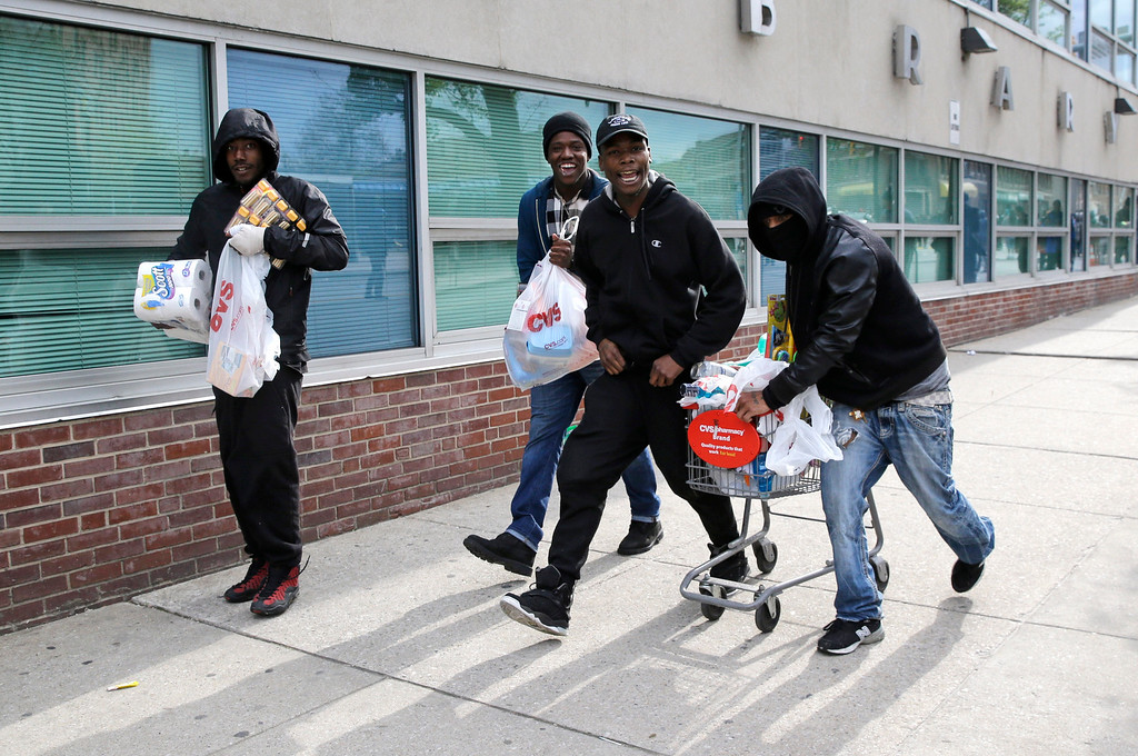 . Men carry items, Monday, April 27, 2015, during unrest following the funeral of Freddie Gray in Baltimore. Gray died from spinal injuries about a week after he was arrested and transported in a Baltimore Police Department van. (AP Photo/Patrick Semansky)