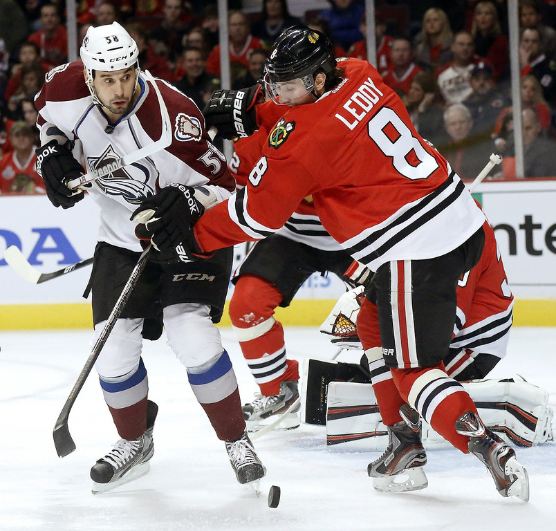 . Chicago Blackhawks defenseman Nick Leddy (8) and Colorado Avalanche left wing Patrick Bordeleau battle for a loose puck during the first period of an NHL hockey game, Wednesday, March 6, 2013, in Chicago. (AP Photo/Charles Rex Arbogast)
