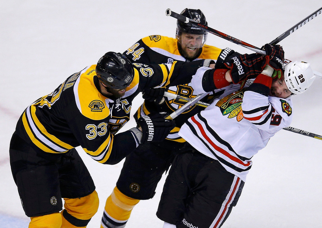 . Boston Bruins\' Zdeno Chara (33) and Dennis Seidenberg push Chicago Blackhawks\' Bryan Bickell during the third period in Game 3 of their NHL Stanley Cup Finals hockey series in Boston, Massachusetts, June 17, 2013. REUTERS/Brian Snyder