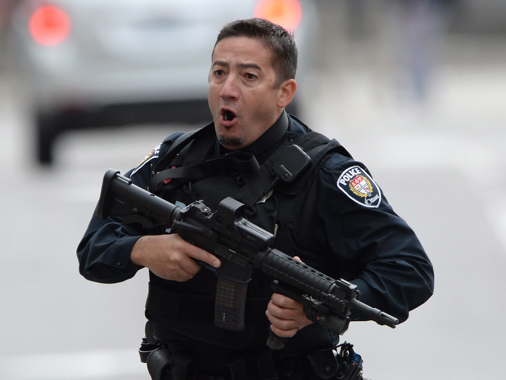 . An Ottawa police officer runs with his weapon drawn outside Parliament Hill in Ottawa on Wednesday Oct. 22, 2014.  A soldier standing guard at the National War Memorial was shot by an unknown gunman and people reported hearing gunfire inside the halls of Parliament. Prime Minister Stephen Harper was rushed away from Parliament Hill to an undisclosed location, according to officials. (AP Photo/The Canadian Press, Sean Kilpatrick)