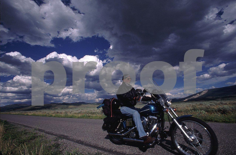 Rider on a Harley Davidson motorcycle riding through the Grand Tetons, WY after a severe thunderstorm