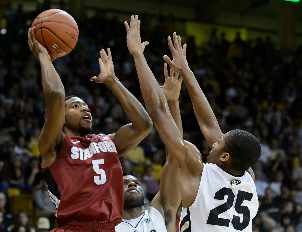 . Stanford\'s Chasson Randle takes a shot over Jeremy Adams, center, and Spencer Dinwiddie, No. 25, during a game against the University of Colorado on Thursday, Jan. 24, at the Coors Event Center on the CU campus in Boulder. Jeremy Papasso/ Camera