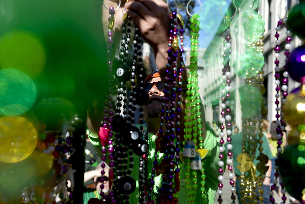 . Aaron Sines, of Statesboro,Ga. looks through an assortment of beads before the St. Patrick\'s Day Parade in Savannah, Ga., Tuesday, March 17, 2015. (AP Photo/Savannah Morning News, Ian Maule)