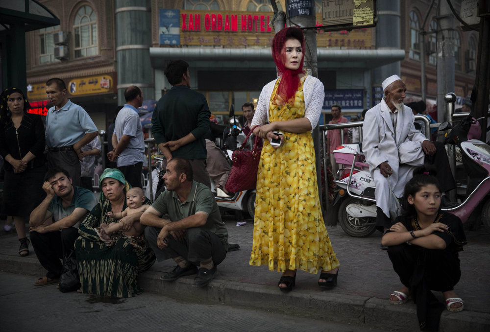 . Uyghurs wait at a bus stop on July 27, 2014 in old Kashgar, Xinjiang Province, China. Nearly 100 people have been killed in unrest in the restive Xinjiang Province in the last week in what authorities say is terrorism but advocacy groups claim is a result of a government crackdown to silence opposition to its policies. China\'s Muslim Uyghur ethnic group faces cultural and religious restrictions by the Chinese government. Beijing says it is investing heavily in the Xinjiang region but Uyghurs are increasingly dissatisfied with the influx of Han Chinese and uneven economic development.  (Photo by Kevin Frayer/Getty Images)