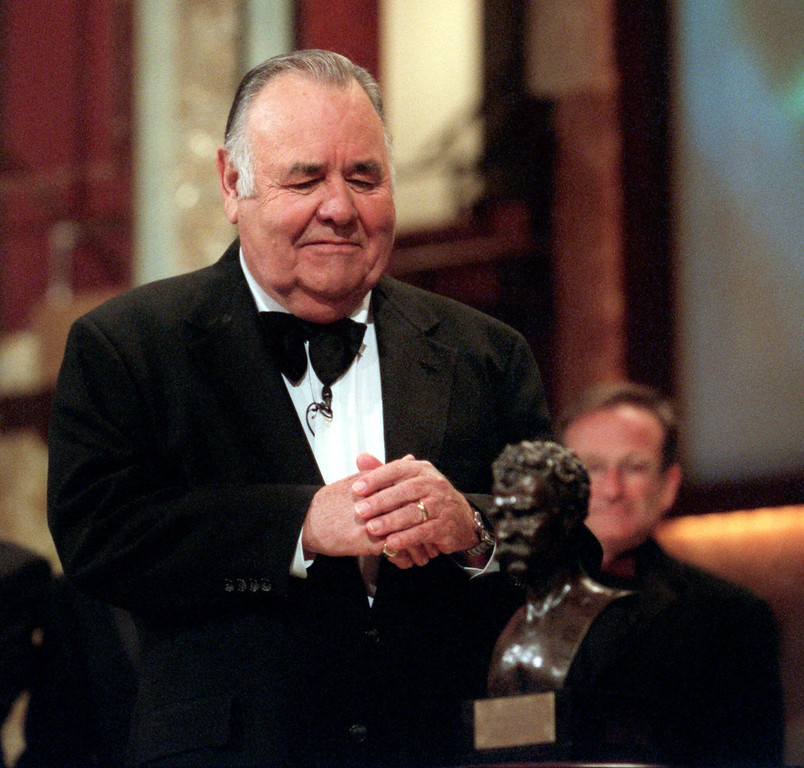 """. Comedian Jonathan Winters looks at the \""""Mark Twain Prize\"""" after he received the award at the Kennedy Center in Washington, Wednesday, Oct. 20, 1999. The Kennedy Center organized the celebration of American humor and created the award to recognize \""""those who create humor from their uniquely American experiences.\"""" In the background is comedian Robin Williams. (AP Photo/Nick Wass)"""