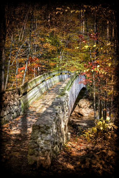 Wooden bridge crossing a mountain stream during autumn.