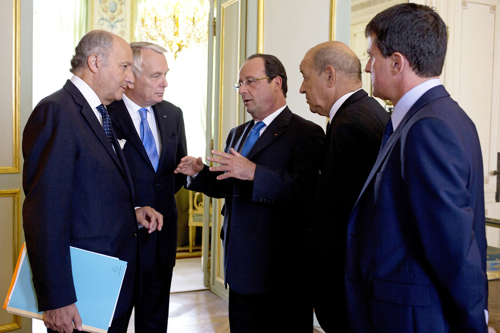 . French President Francois Hollande, center, gestures as he speaks with his ministers prior to a defense meeting on the situation in Syria, at the Elysee Palace in Paris, Wednesday Aug. 28, 2013. From left: foreign minister Laurent Fabius, prime minister Jean-Marc Ayrault, Francois Hollande, defense minister Jean-Yves Le Drian and interior minister Manuel Valls. Francois Hollande said Tuesday, that France was prepared to take action against those responsible for gassing people in Syria.(AP Photo/Kenzo Tribouillard, Pool)