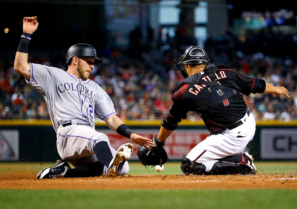 . Colorado Rockies\' Trevor Story scores on an RBI double by Gerardo Parra as Arizona Diamondbacks catcher Welington Castillo (7) makes the catch during the third inning of a baseball game, Saturday, April 30, 2016, in Phoenix. (AP Photo/Matt York)