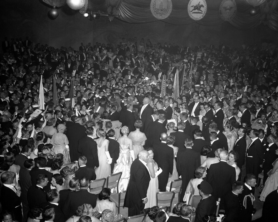 . President Dwight Eisenhower smiles and waves from crowded ballroom floor during his appearance at inaugural ball at the Sheraton Park Hotel in Washington on Jan. 21, 1957. Ike made the rounds of four balls held throughout the city as climax to inaugural doings. (AP Photo)