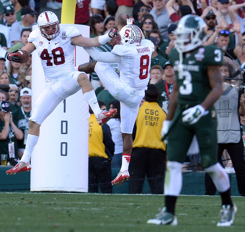 . Stanford\'s Kevin Anderson (48) reacts with teammate Stanford safety Jordan Richards (8) after intercepting a pass and running for a touchdown as Michigan State wide receiver Macgarrett Kings Jr. (3) walks towards hid bench in the first half of the 100th Rose bowl game in Pasadena, Calif., on Wednesday, Jan.1, 2014. 